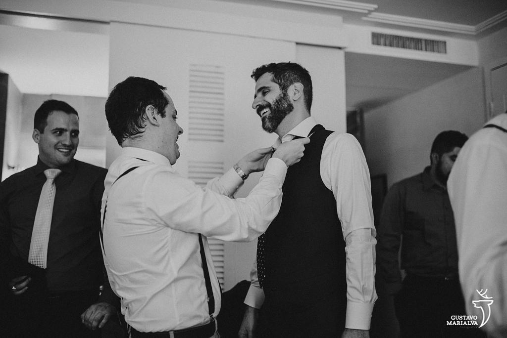 padrinho ajeitando a gravata do noivo no making of do casamento