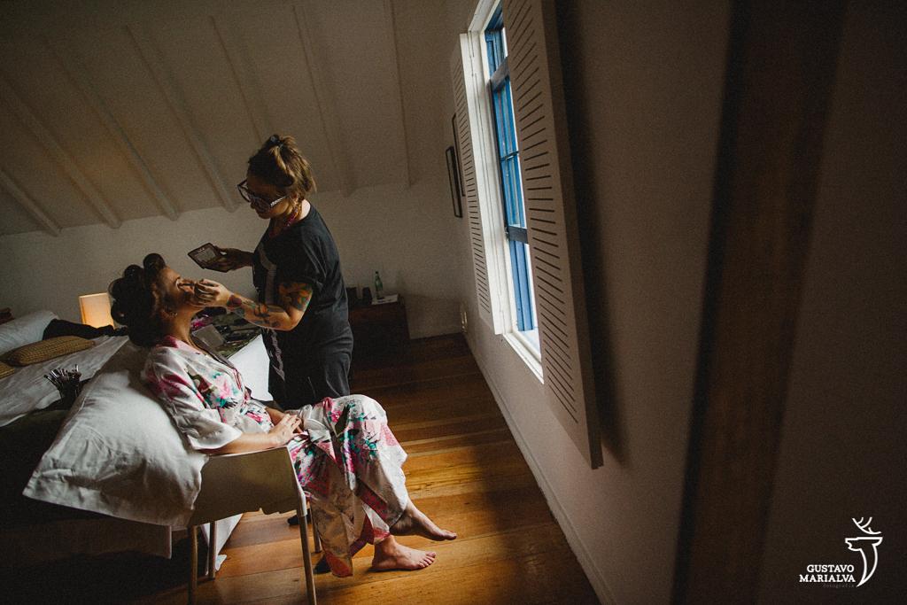 Noiva se maquiando no making of do casamento