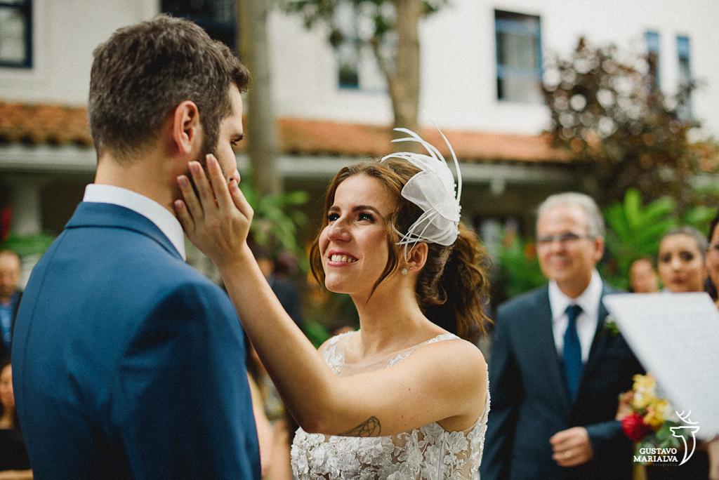 noiva acariciando o noivo na cerimônia de casamento