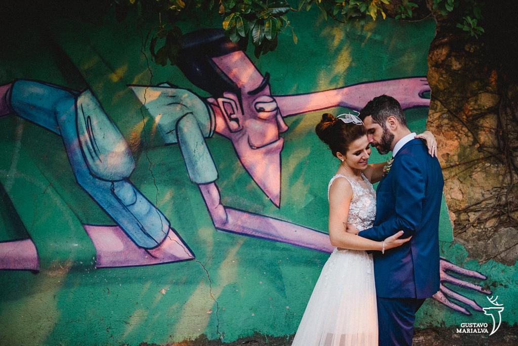 noivos posando em frente a parede com grafite