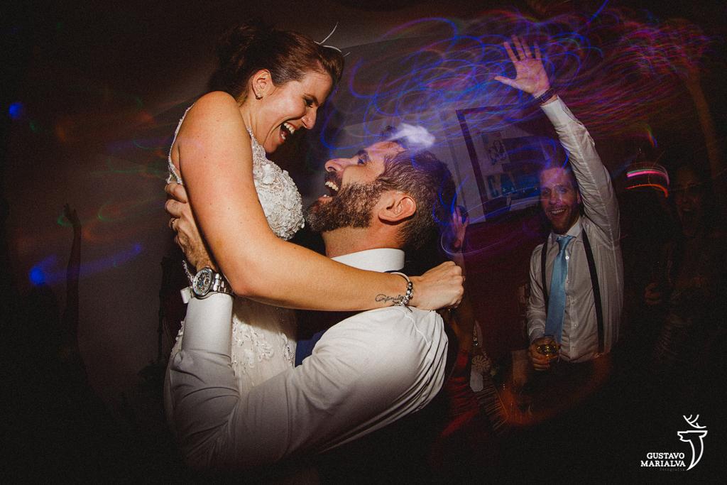 noivo carregando a noiva no colo