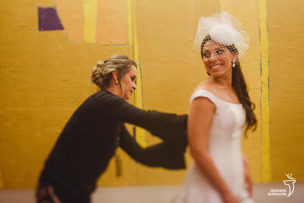 tia da noiva fechando o vestido de casamento