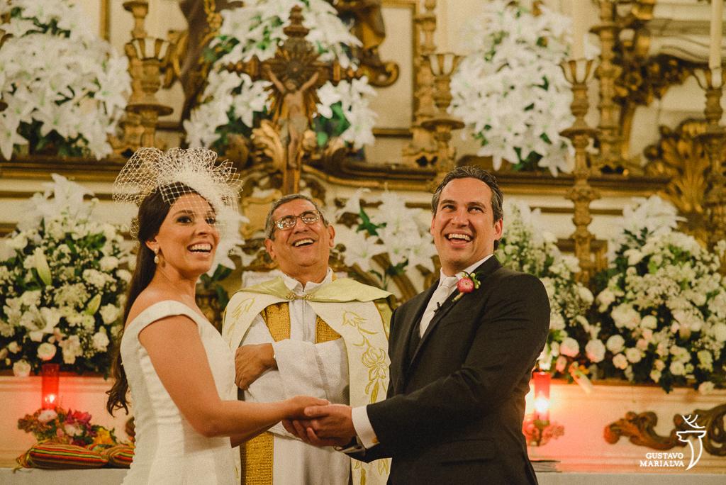 noivos e padre sorrindo na cerimônia de casamento