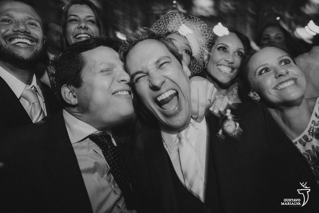 noivos e convidados sorrindo durante a festa de casamento