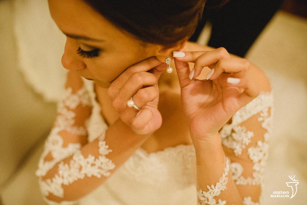 noiva colocando o brinco durante o making of de casamento