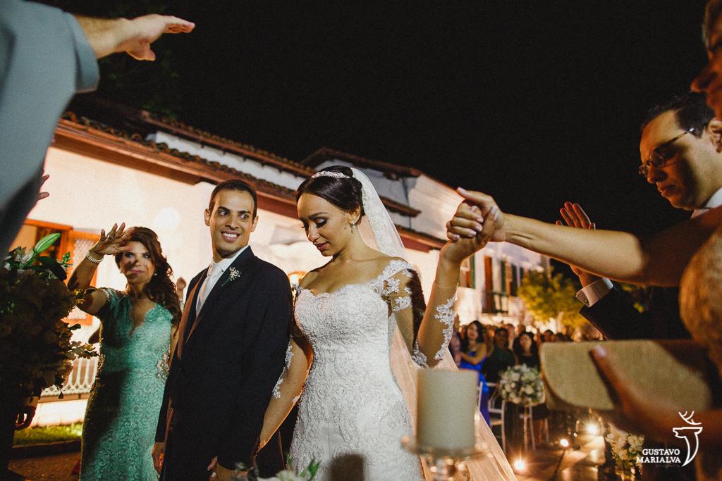 noiva segurando a mão da mãe na cerimônia de casamento