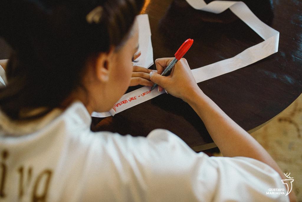 noiva escrevendo na barra do vestido durante o making of de casamento