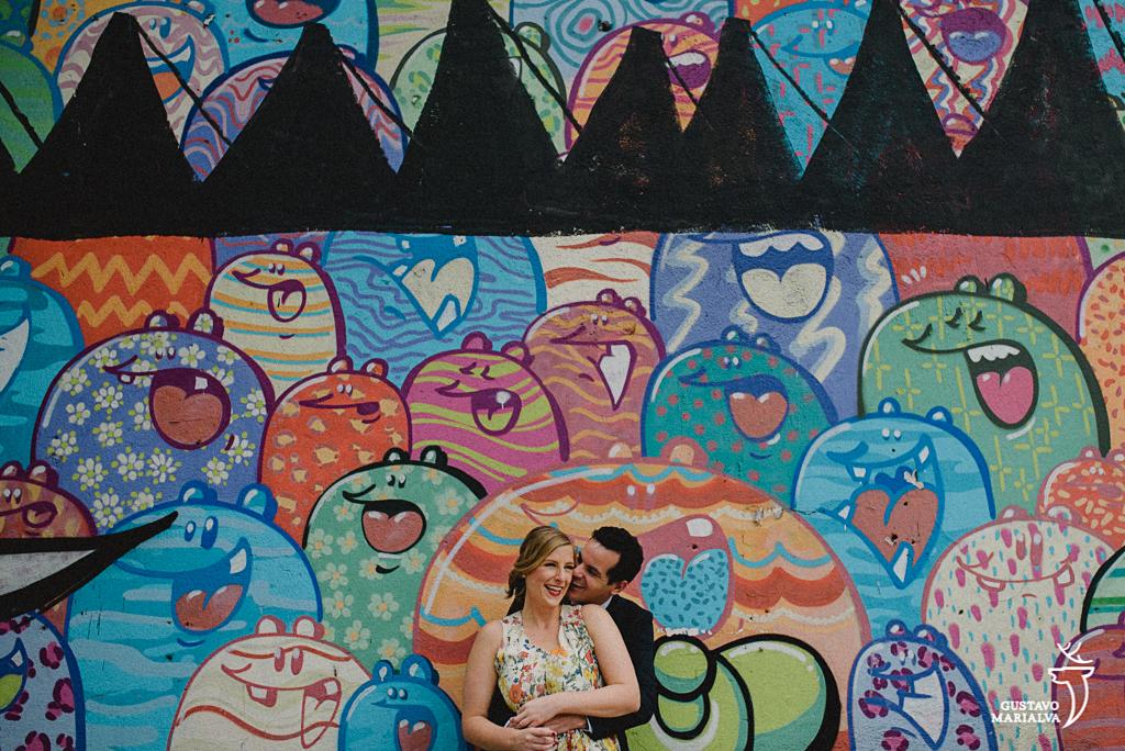 noivos posando em frente a grafite durante book de casal
