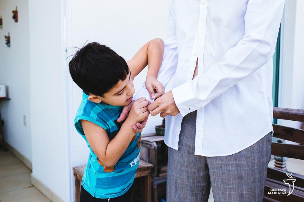 filho da noiva fechando o botão da camisa do noivo durante o making of do casamento
