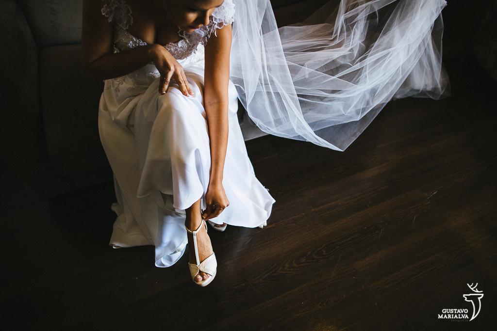 noiva colocando o sapato durante o making of do casamento