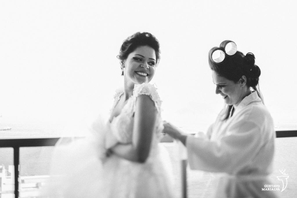 mãe da noiva fechando o vestido de casamento durante o making of do casamento
