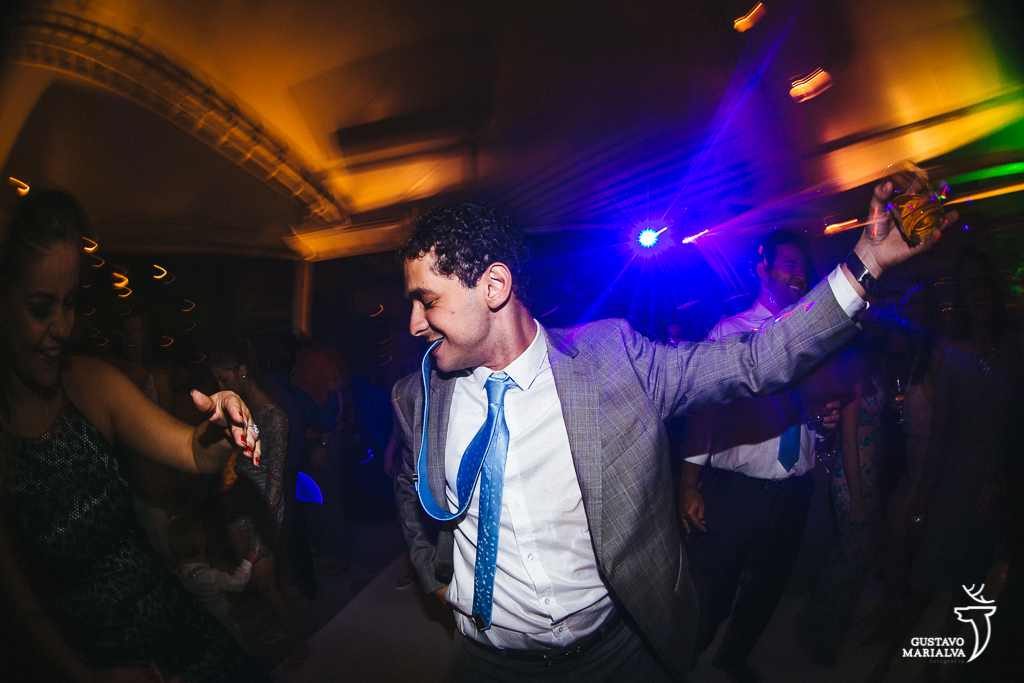 noivo pulando durante a festa de casamento