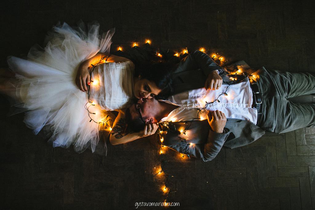 noivos abraçados com luz de natal durante book de casal