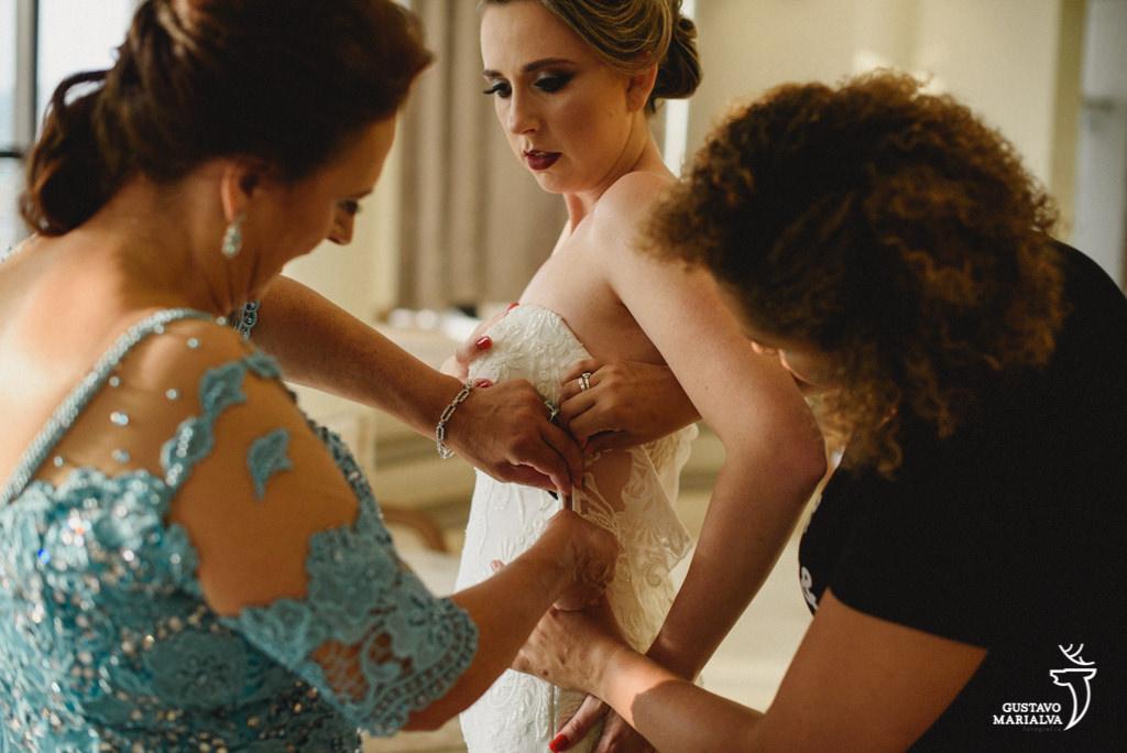 noiva colocando o vestido durante making of de casamento
