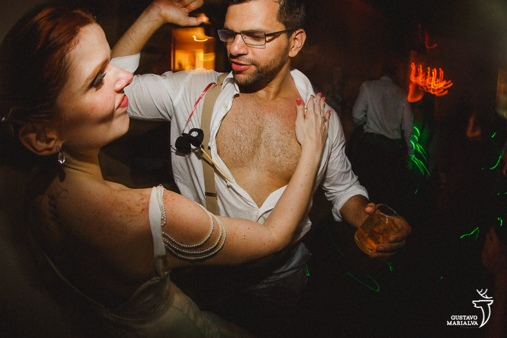 noiva tirando a camisa do noivo na festa de casamento
