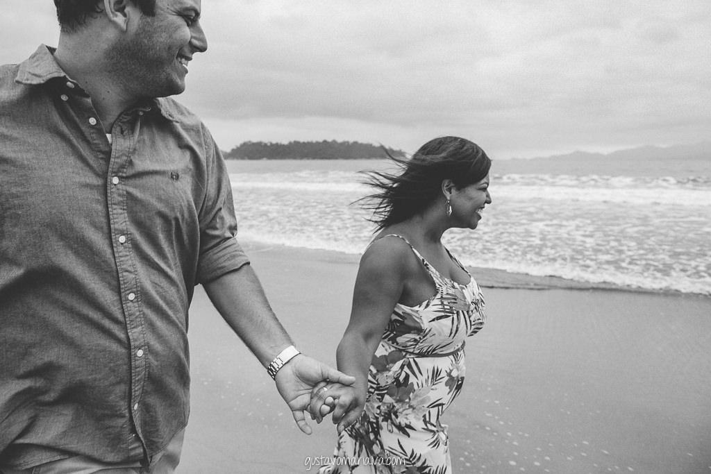 casal correndo na praia durante book de casal