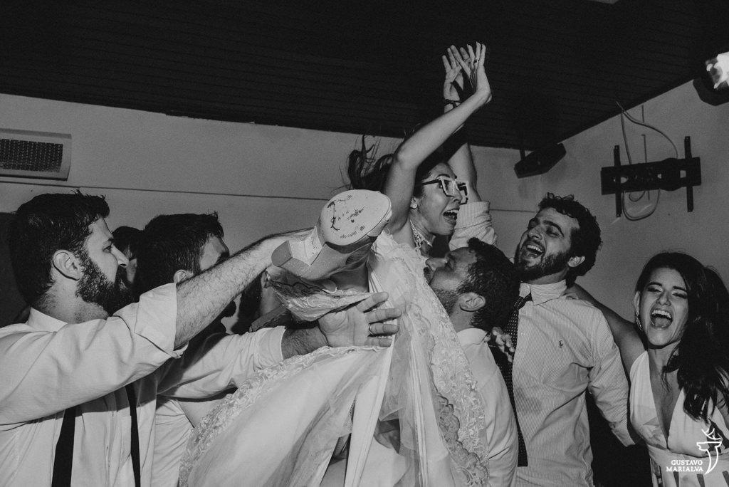 noiva sendo jogada para o alto na festa de casamento