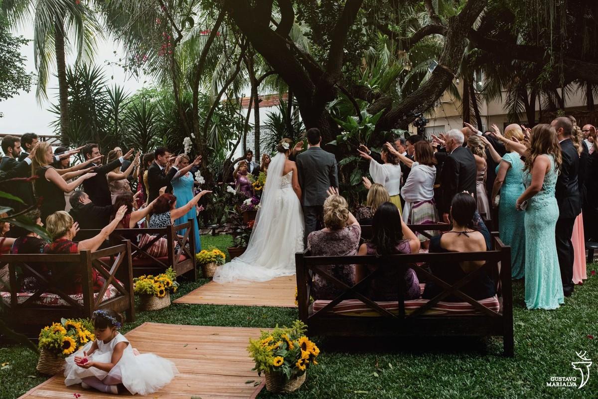 noivos sendo abençoados pelos convidados durante a cerimônia de casamento