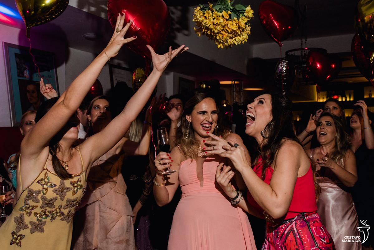 convidadas disputando o buquê na festa de casamento