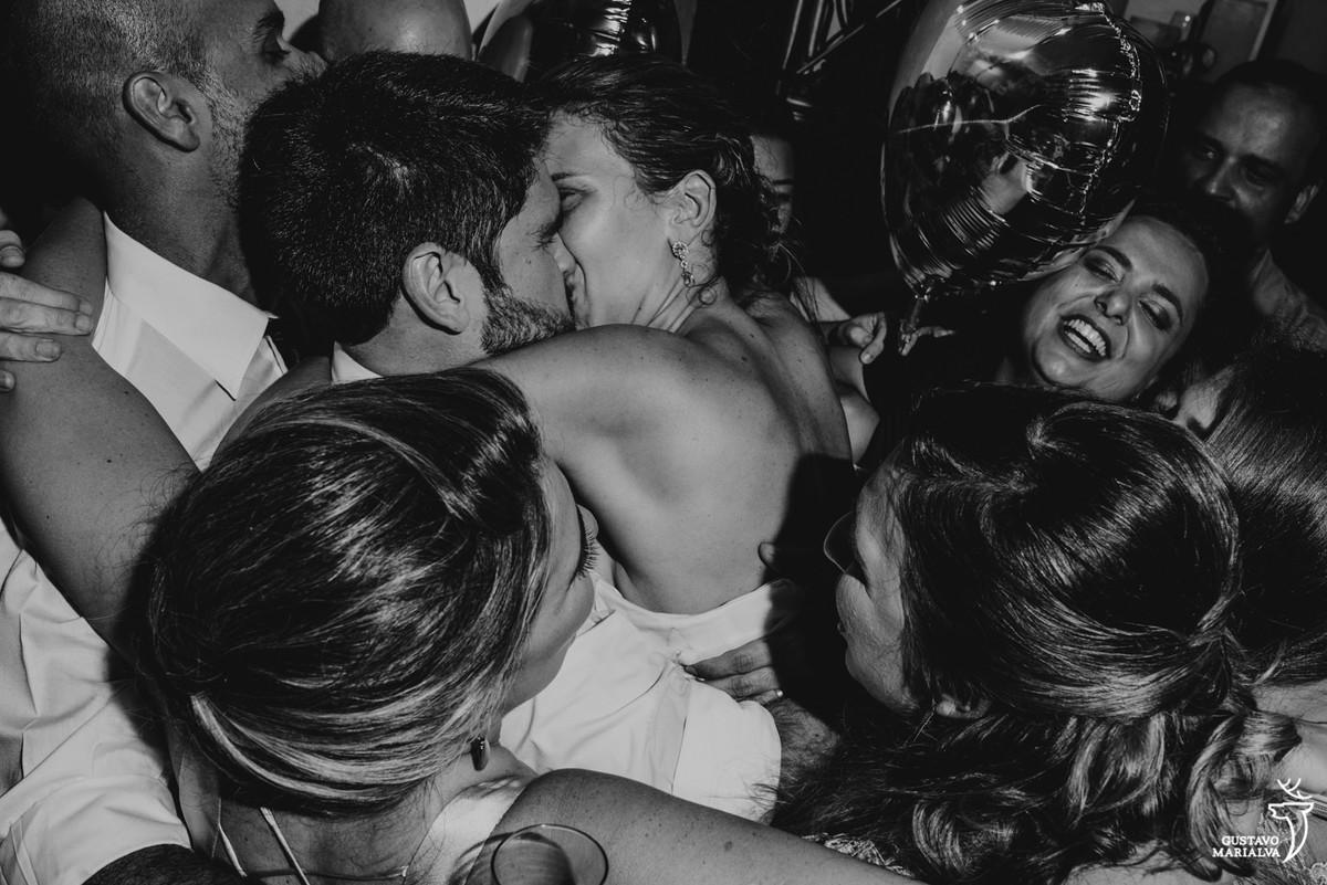 noivos se beijando e sendo abraçados pelos convidados na festa de casamento