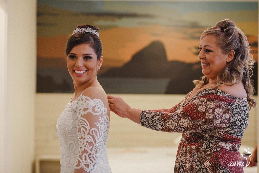 mãe fechando o vestido da noiva durante o making of de casamento
