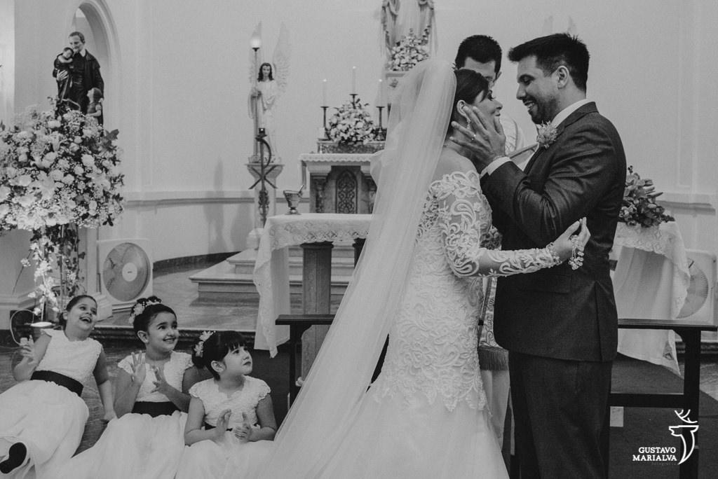 noivos se beijando e daminhas emocionadas na cerimônia de casamento