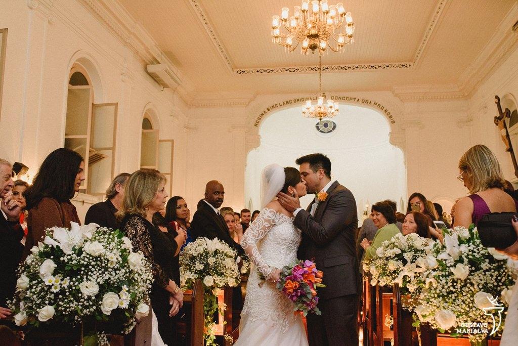 noivos se beijando na saída da cerimônia de casamento