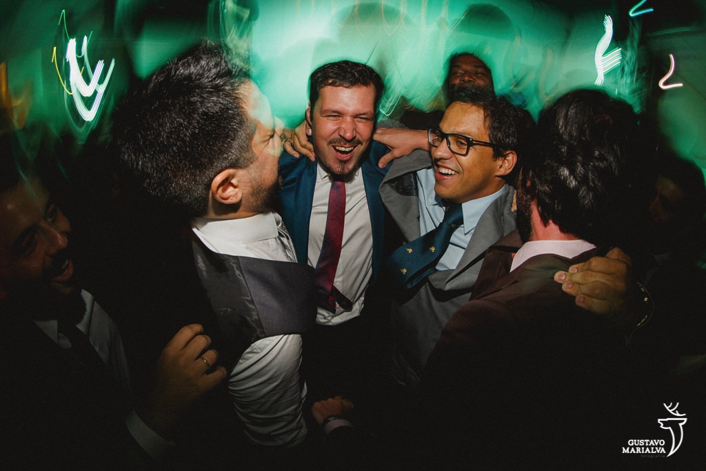 noivo e amigos pulando na festa de casamento