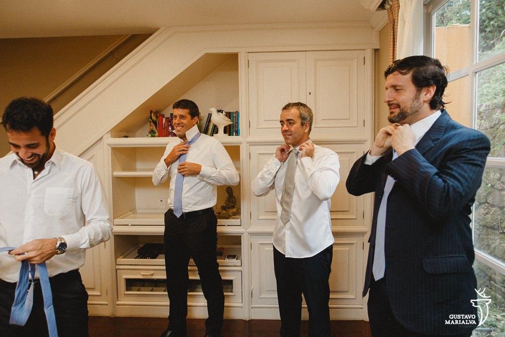 noivo e padrinhos colocando a gravata durante making of de casamento