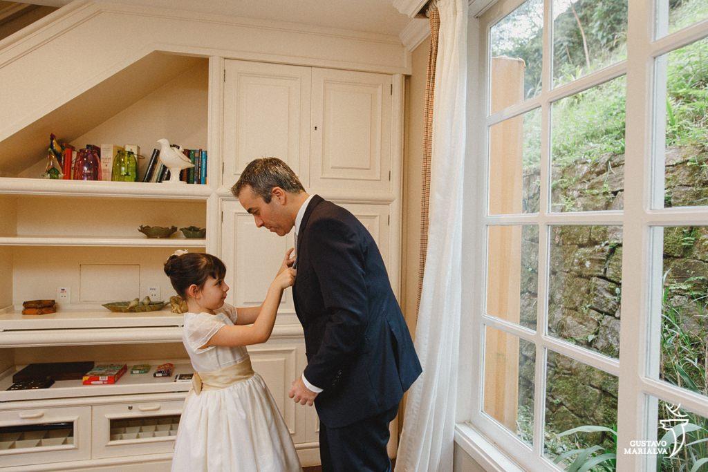 filha do noivo arrumando a gravata durante making of de casamento