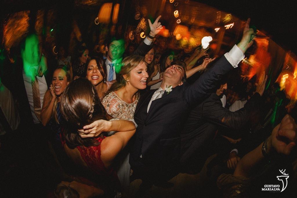 noivos e convidados vibrando na festa de casamento