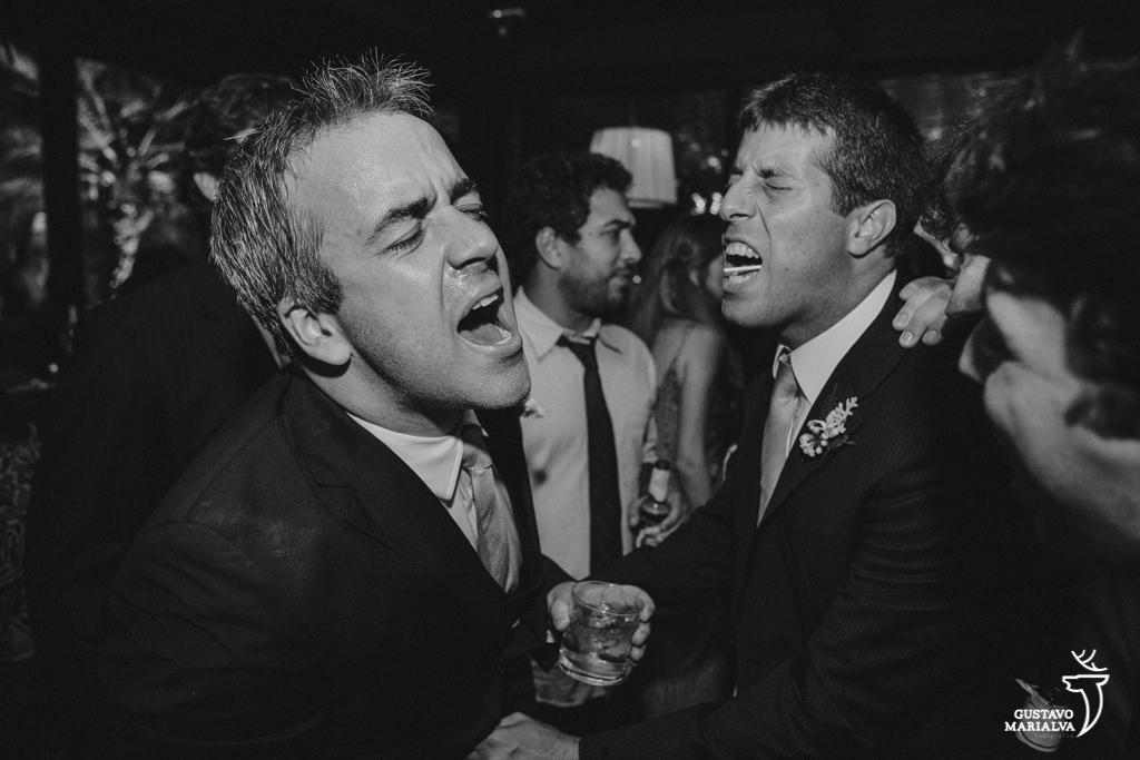 noivo e padrinho cantando na festa de casamento