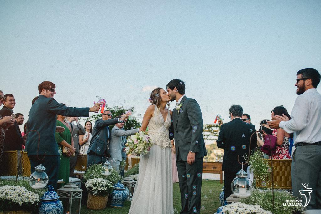 noivos se beijando na saída da cerimônia de casamento com bolinhas de sabão
