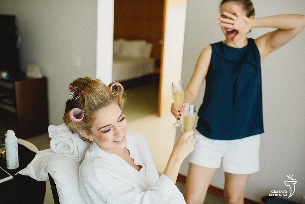 noiva e irmã brindando durante o making of do casamento