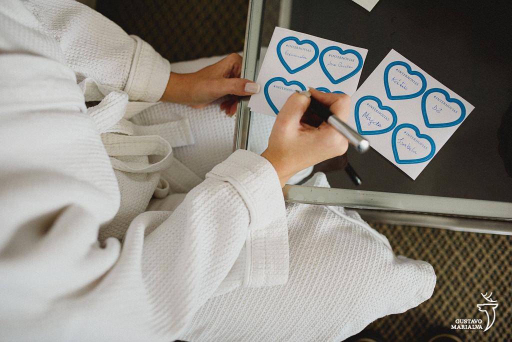 noiva escrevendo os nomes na barra do vestido durante o making of do casamento
