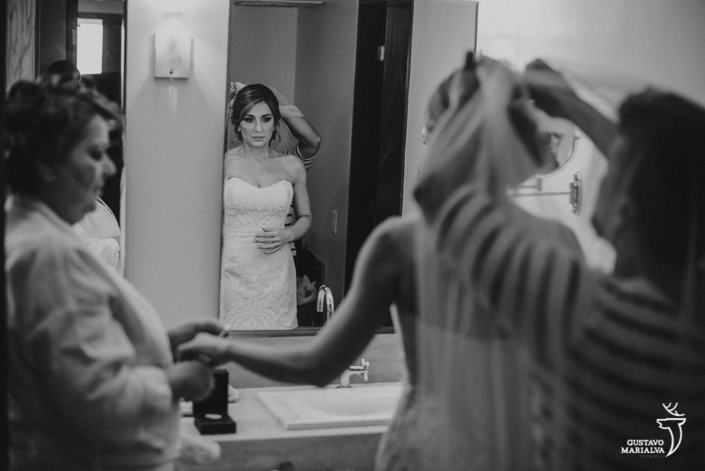 noiva colocando o véu e dando as mãos para a mãe durante o making of do casamento