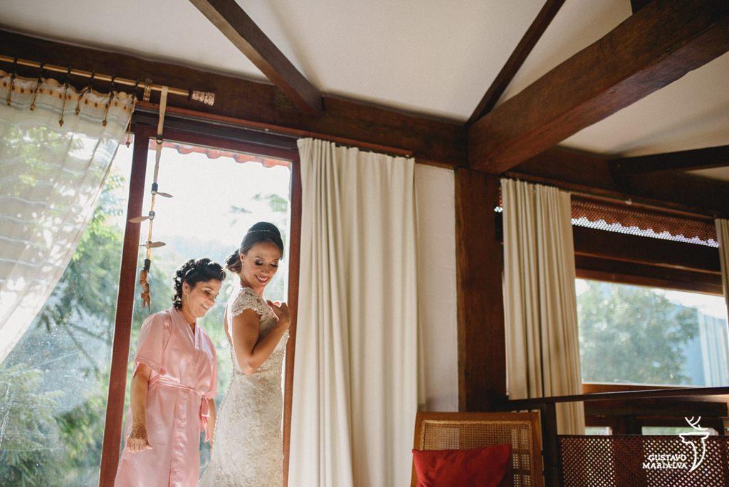 noiva fechando o vestido durante o making of do casamento
