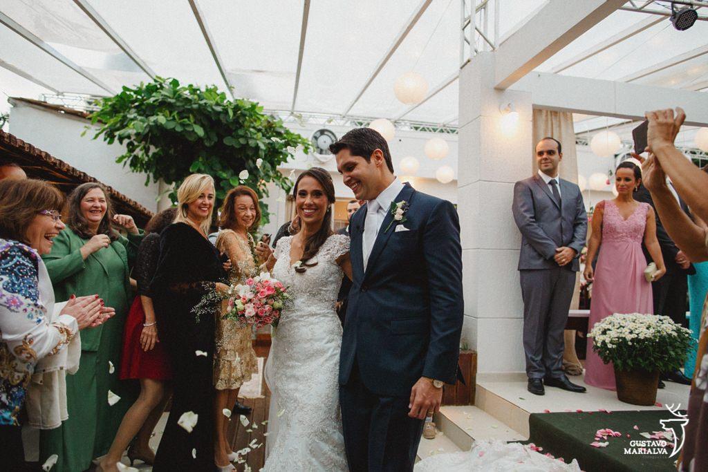 noivos sorrindo na saída da cerimônia de casamento