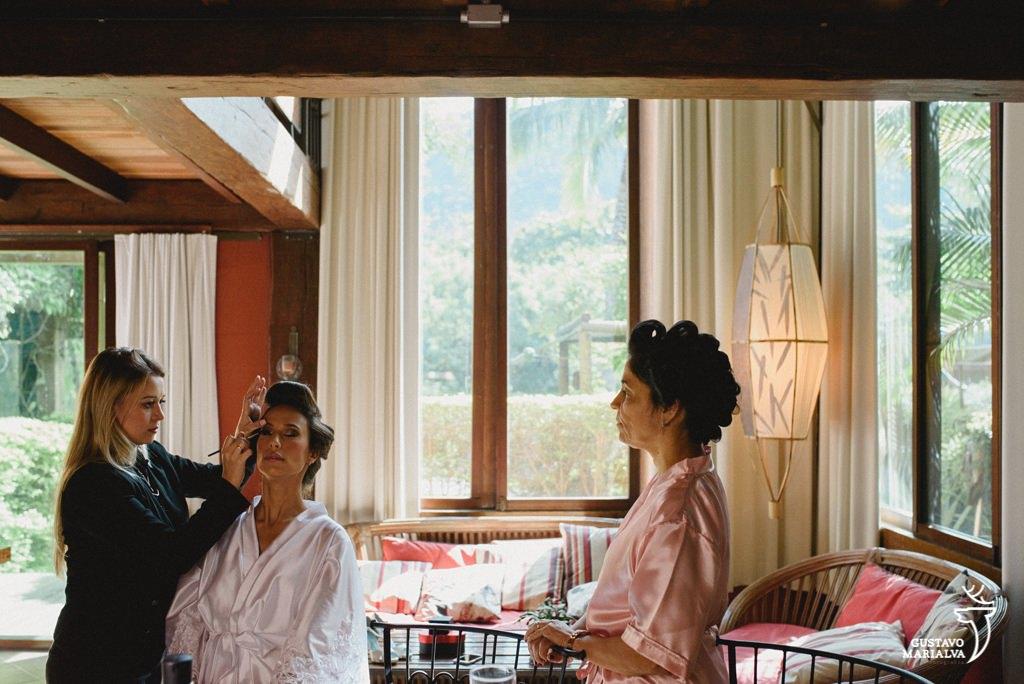 noiva sendo maquiada e mãe observando durante o making of do casamento