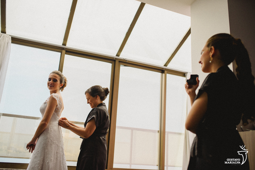 mãe fechando o vestido da noiva e irmão olhando emocionada durante o making of do casamento