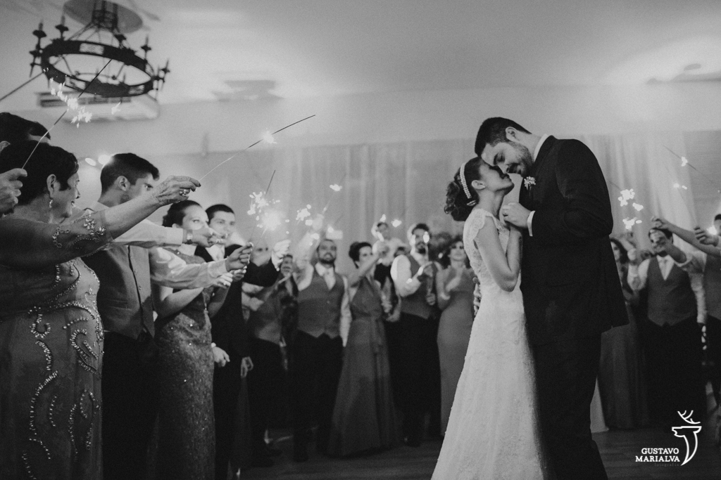 noivos dançando com padrinhos segurando sparkles na festa de casamento