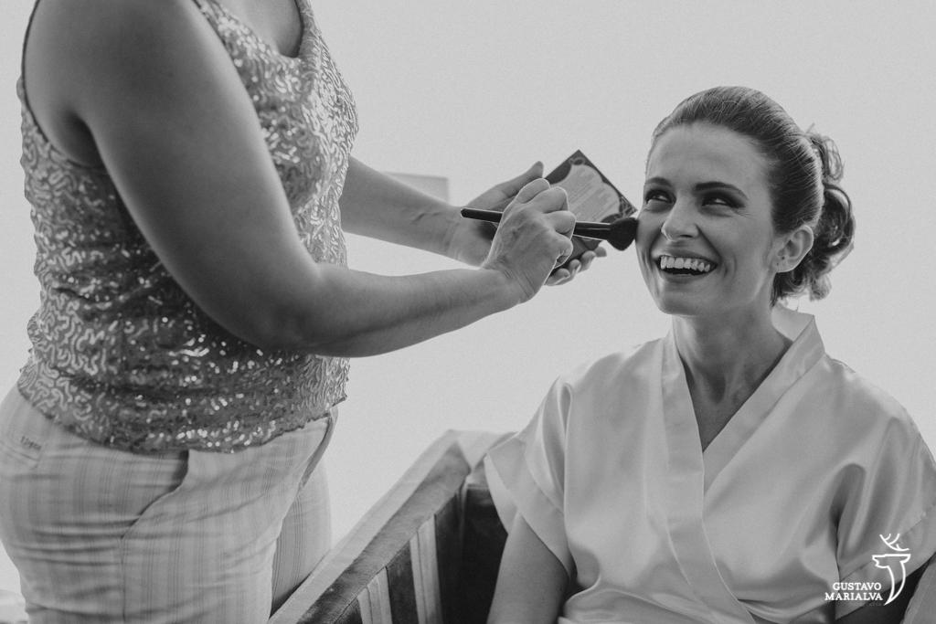 noiva sorrindo e se maquiando durante o making of do casamento
