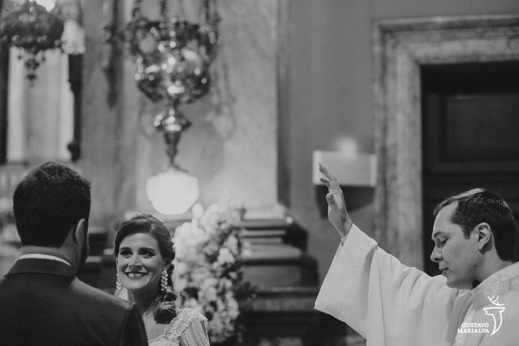 padre abençoando os noivos na cerimônia de casaemnto