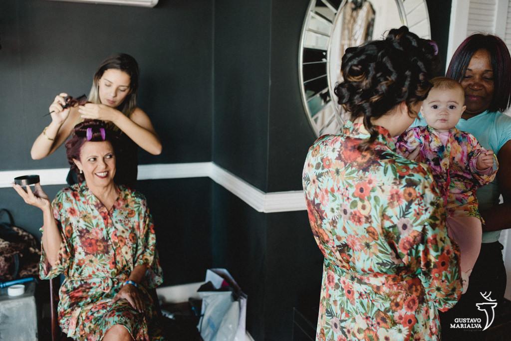 mãe da noivando maquiada e olhando a neta durante o making of de casamento