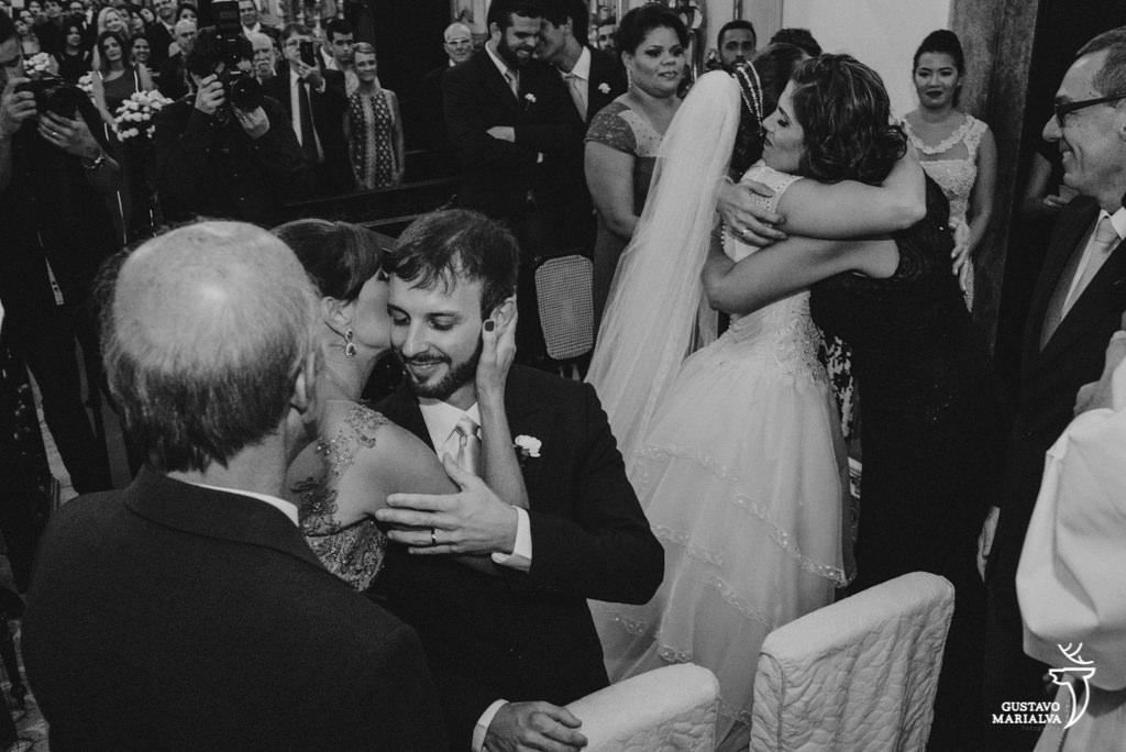 mães abraçando os noivos durante a cerimônia de casamento