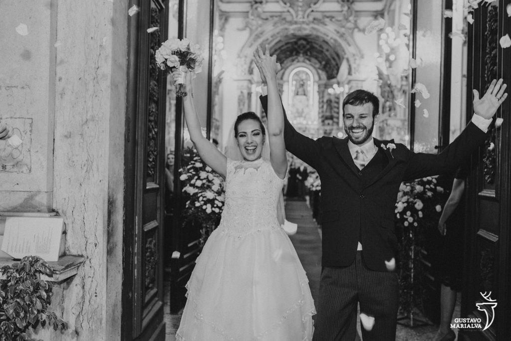 noivos comemorando o casamento na saída da cerimônia