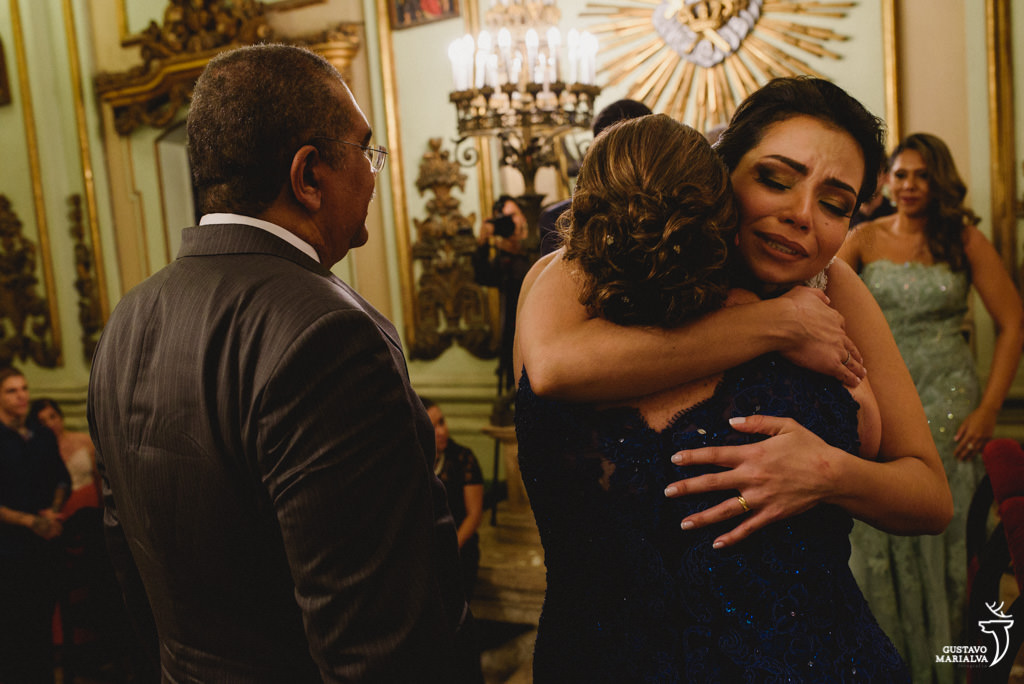 noiva emocionada abraçando a mãe do noivo na cerimônia do casamento