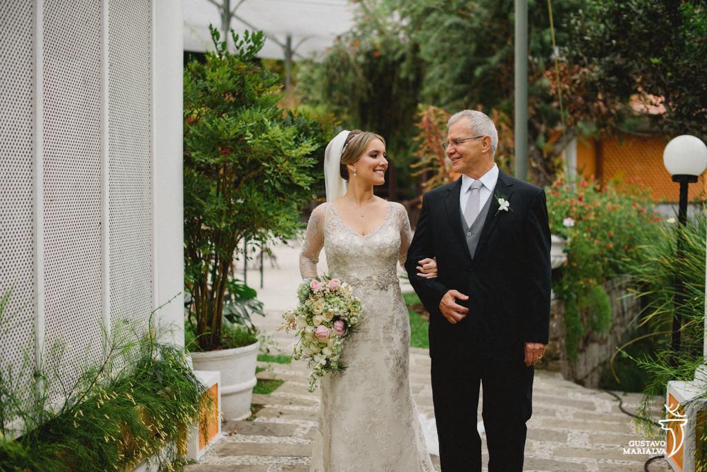 noiva emocionada com o pai entrando na cerimônia