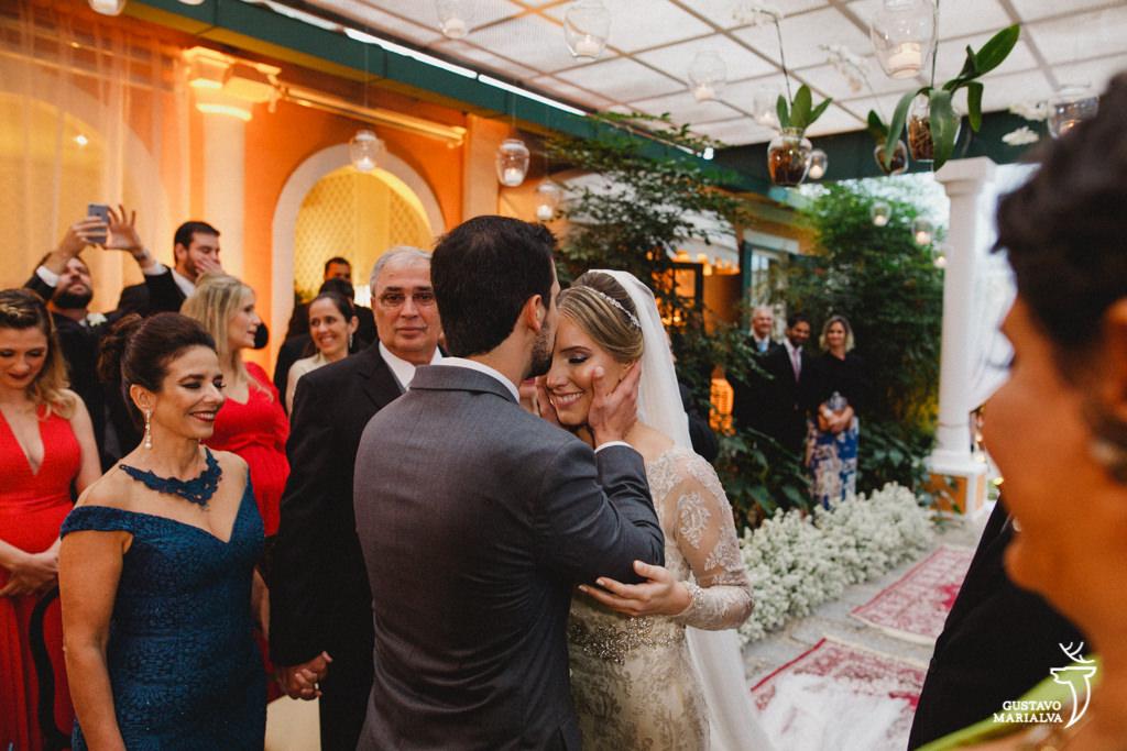 noivo beijando a testa da noiva durante a cerimônia de casamento
