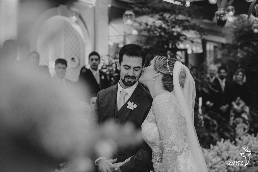 noiva beijando o noivo durante a cerimônia de casamento